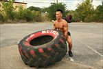 Trainer lifting big tire pose...