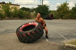 Trainer flipping big tire exercise