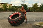 Trainer picking up to flip big tire